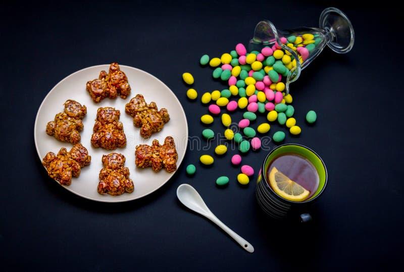 自创熊形状糖果、玻璃花瓶用五颜六色的糖果和茶 库存照片