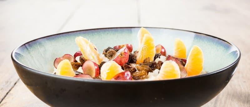 自创燕麦粥用葡萄、橙色段和葡萄干在一个碗在葡萄酒木桌上 健康早餐-纤维的来源 免版税库存照片