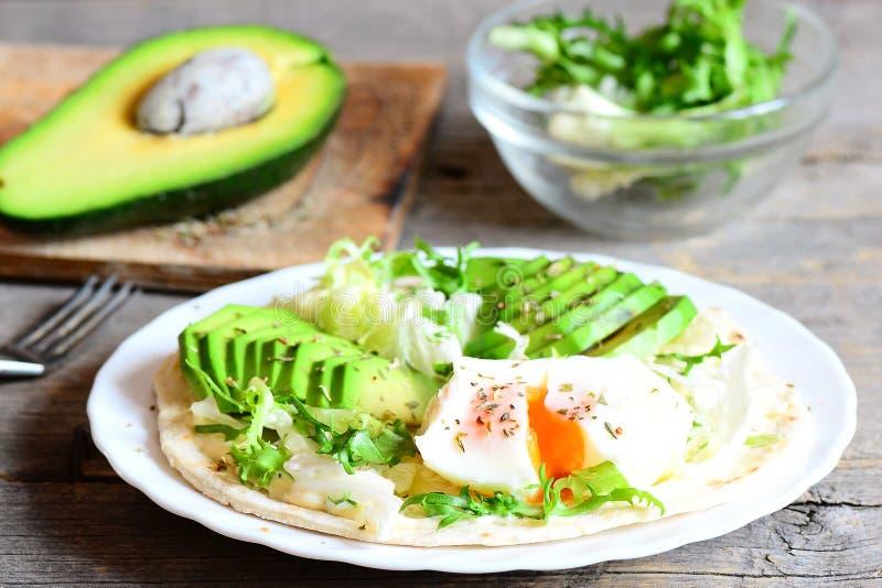 自创玉米粉薄烙饼用一个荷包蛋、鳄梨片、napa圆白菜、沙拉混合、调味汁和香料在板材 免版税图库摄影