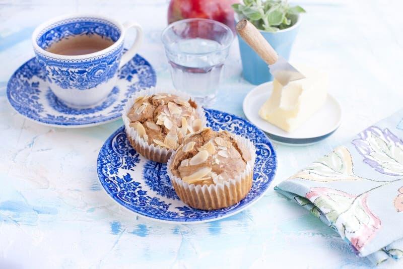 自创甜松饼用早餐茶和一杯的杏仁在葡萄酒蓝色盘的水 果子和油 自由空间为 库存照片