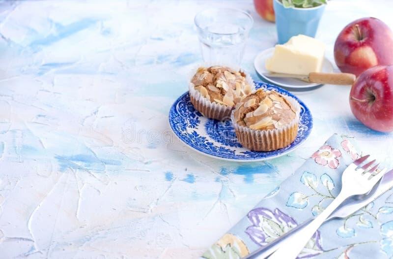 自创甜松饼用早餐茶和一杯的杏仁在葡萄酒蓝色盘的水 果子和油 自由空间为 库存图片