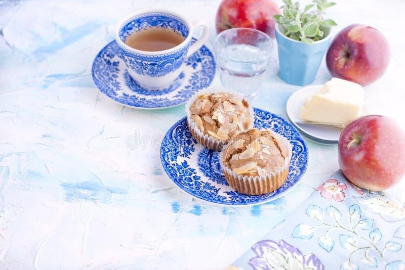 自创甜松饼用早餐茶和一杯的杏仁在葡萄酒蓝色盘的水 果子和油 自由空间为 免版税库存图片