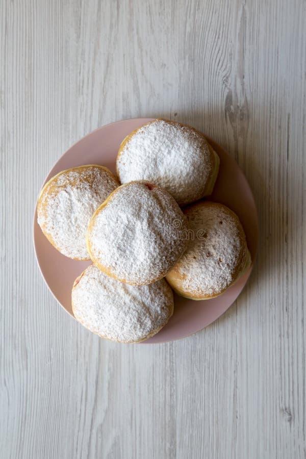 自创甜油炸圈饼用在桃红色板材的糖粉在白色木背景,顶视图 平的位置,顶上,从上面 免版税图库摄影