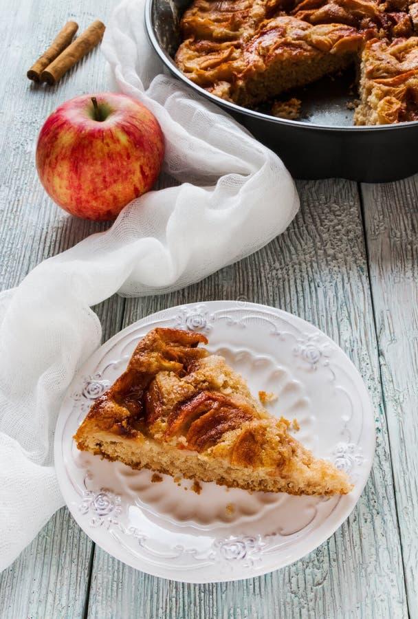 自创甜苹果片断和桂香在葡萄酒白色板材结块 在烘烤盘的饼和在木背景的新鲜水果 库存照片