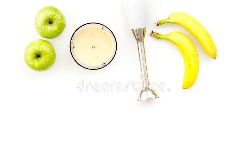 自创的婴儿食品 烹调纯汁浓汤用苹果和香蕉与浸没搅拌器 与玩具顶视图空间的白色背景 图库摄影