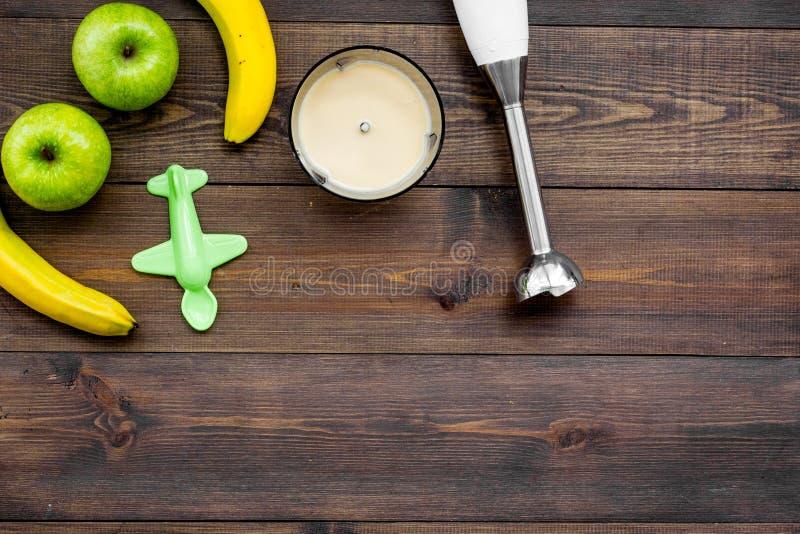 自创的婴儿食品 烹调纯汁浓汤用苹果和香蕉与浸没搅拌器 黑暗的木背景有玩具顶视图 库存图片