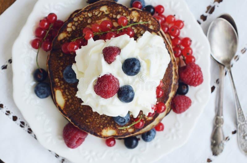 自创稀薄的薄煎饼用被鞭打的奶油色和新鲜的莓果 图库摄影