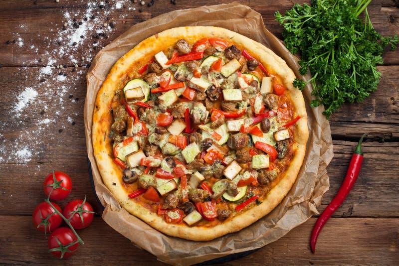 自创素食主义者薄饼用蕃茄、夏南瓜、甜椒、蘑菇和大豆肉在一张老木桌上 顶视图 库存图片