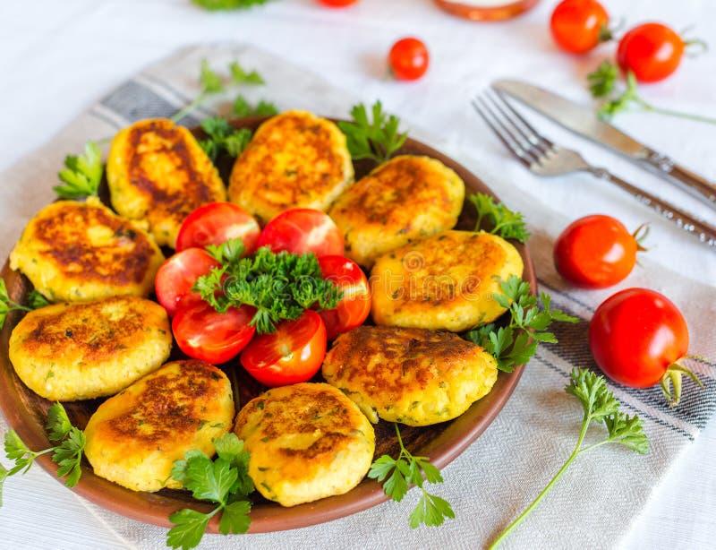 自创红润乳酪和土豆炸肉排,装饰了用新鲜的蕃茄和荷兰芹,在陶瓷板材在餐巾 免版税库存照片