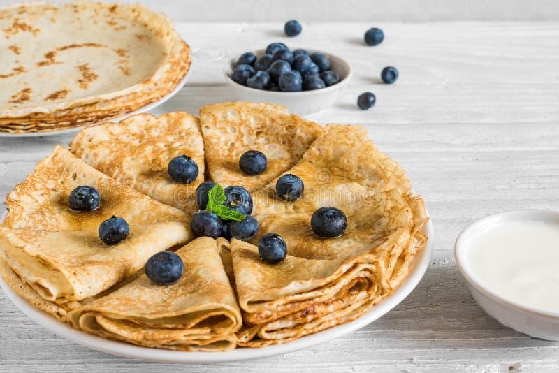 自创绉纱或稀薄的薄煎饼服务用新鲜的蓝莓、酸性稀奶油和薄菏 免版税库存图片