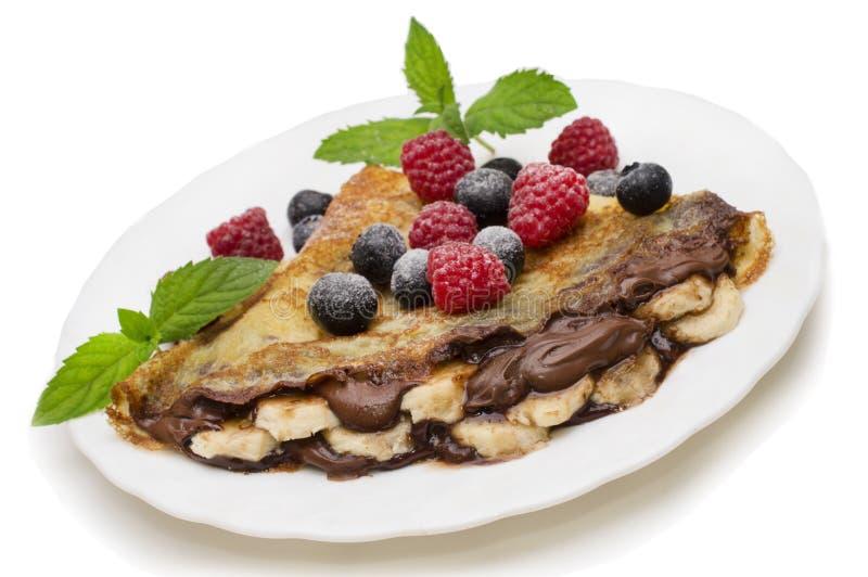 自创绉纱服务与巧克力奶油、新鲜的蓝莓和莓,在白色背景的搽粉的糖 库存照片
