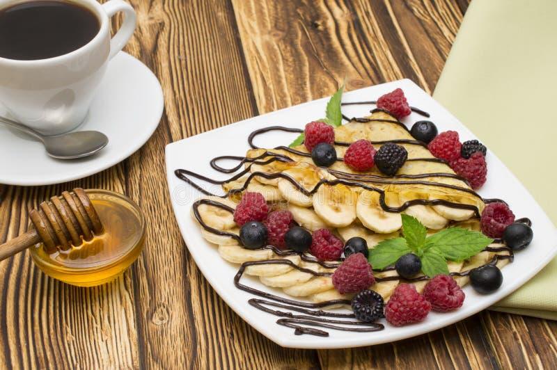 自创绉纱服务与巧克力奶油,香蕉,新鲜的蓝莓,在木背景的莓,薄煎饼 库存照片