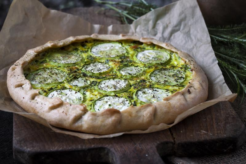 自创绿皮胡瓜和山羊乳干酪饼在黑暗的土气木板背景 库存照片