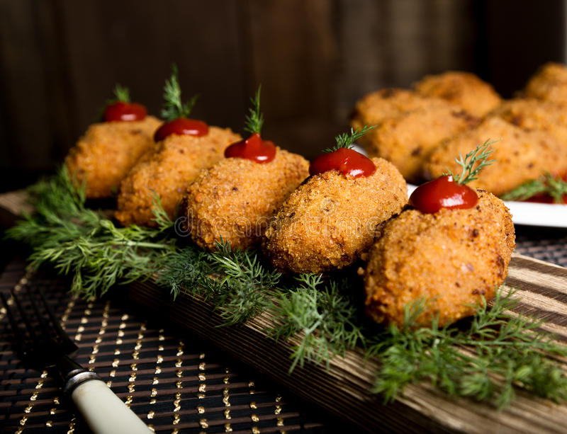 自创肉炸肉排用荷兰芹和番茄酱在木板材 库存照片