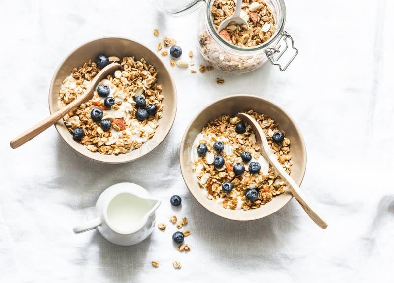 自创花生酱格兰诺拉麦片用希腊酸奶和蓝莓在轻的背景,顶视图 健康能量早餐或snac 免版税库存图片