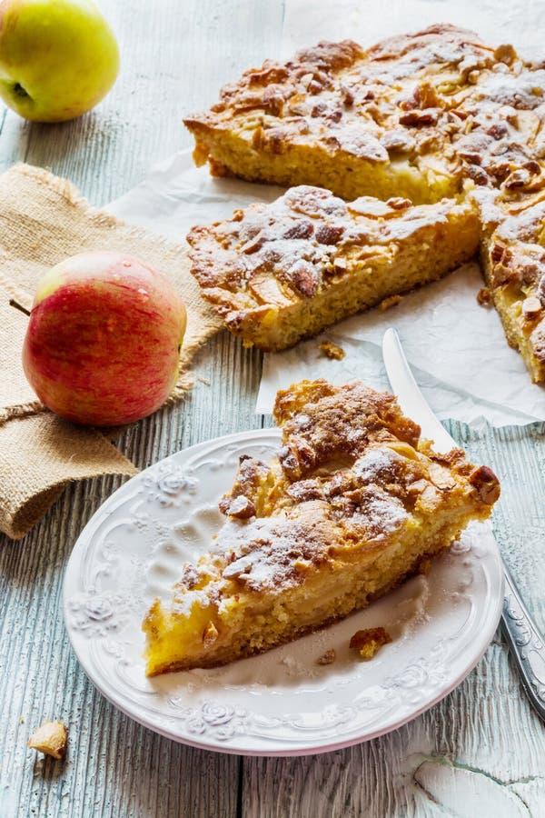 自创苹果和杏仁蛋糕 饼在白色板材和新鲜水果的 免版税库存图片