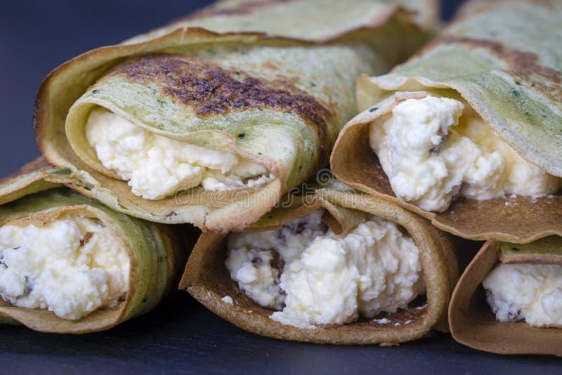 自创薄煎饼用绿色spirulina被充塞的白色酸奶干酪用在黑板岩背景的葡萄干,关闭 免版税图库摄影
