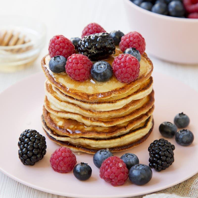 自创薄煎饼用莓果和蜂蜜在一块桃红色板材,侧视图 ?? 免版税图库摄影