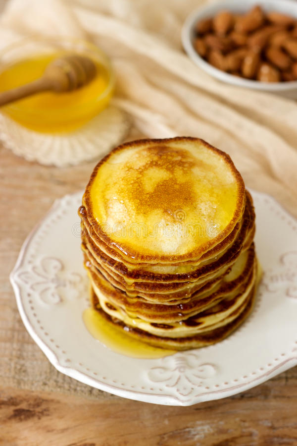 自创薄煎饼用蜂蜜和坚果,早餐 免版税库存图片