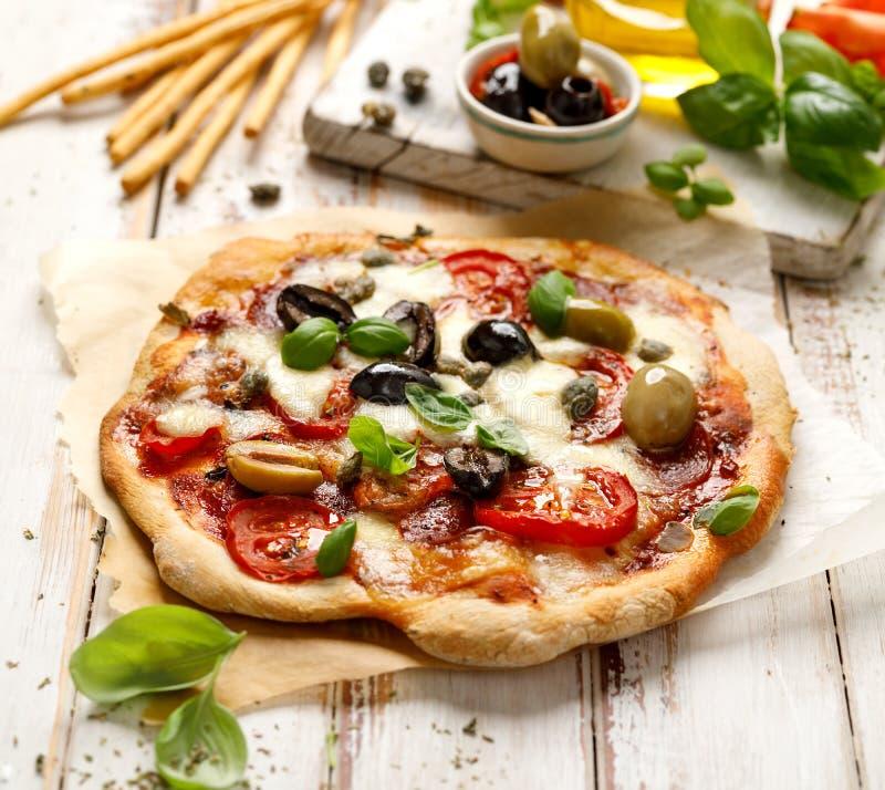 自创薄饼用蕃茄、橄榄、蒜味咸腊肠、无盐干酪乳酪和新鲜的蓬蒿在一张木土气桌上 库存图片