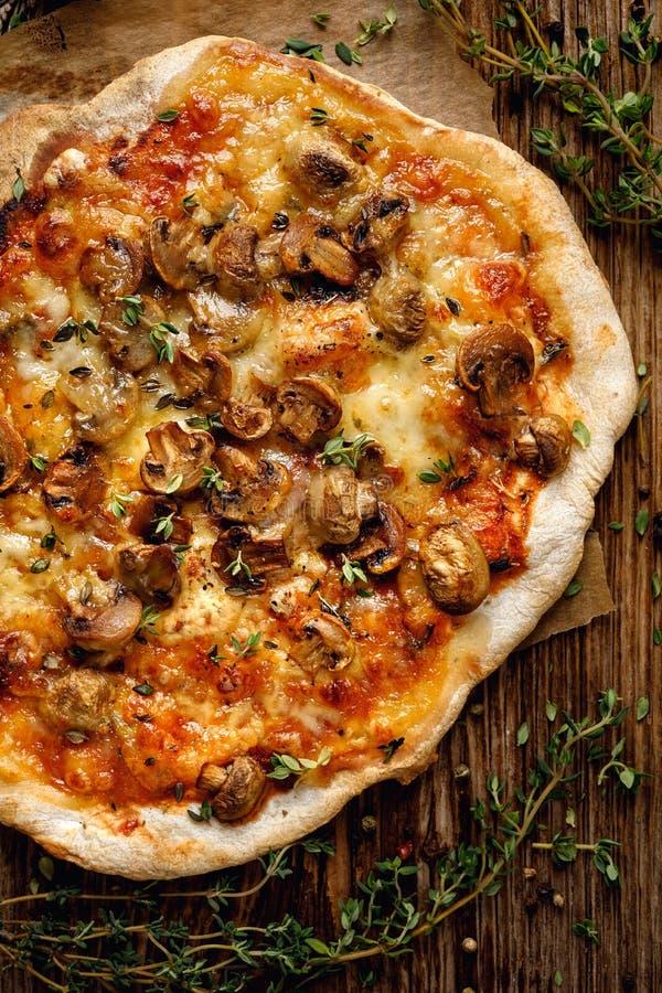 自创薄饼用蘑菇、无盐干酪乳酪和新鲜的麝香草在一张木桌上 免版税库存图片