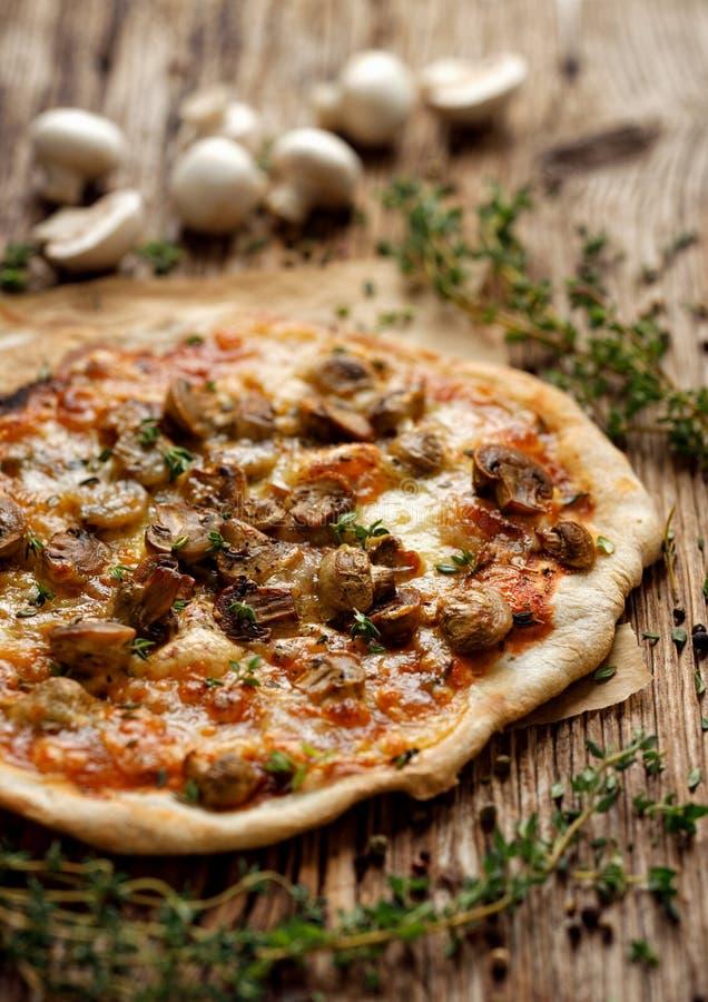 自创薄饼用蘑菇、无盐干酪乳酪和新鲜的麝香草在一张木桌上 免版税库存照片