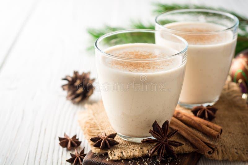 自创蛋黄乳用被磨碎的肉豆蔻和桂香在白色木桌上 传统圣诞节饮料 图库摄影