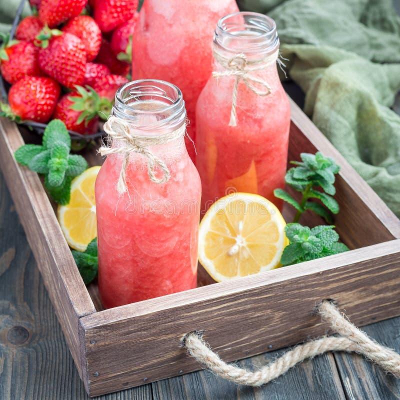 自创被混和的柠檬水用新鲜的草莓、柠檬、冰和薄菏在一个玻璃瓶,方形的格式 图库摄影