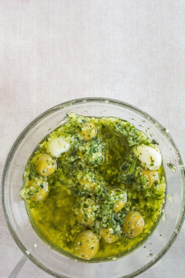自创西班牙样式在油用卤汁泡的挖坑的绿橄榄用大蒜草本和荷兰芹 顶视图 地中海烹调 免版税库存照片