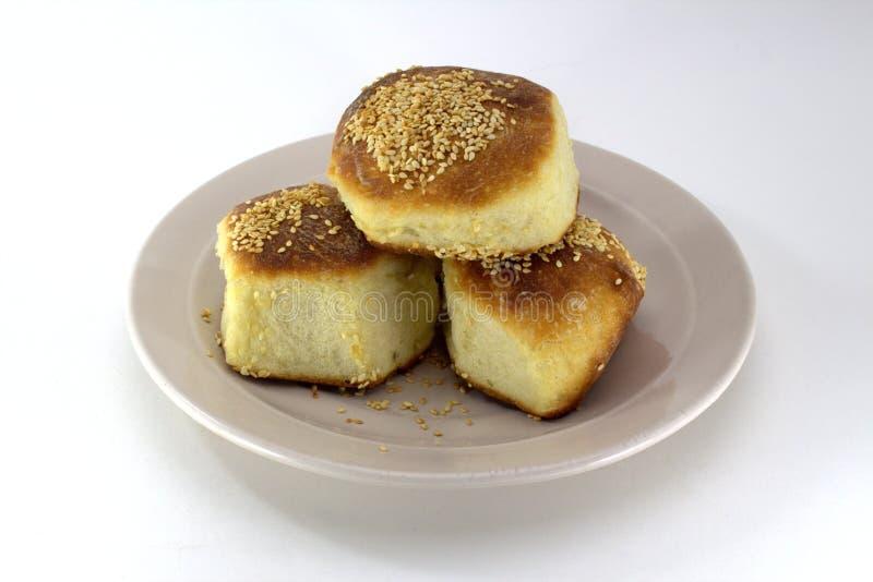 自创酥皮点心,与芝麻籽的红润小圆面包在白色背景的一块珍珠板材 库存照片