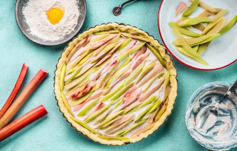 自创酥皮糕点酥皮点心大黄饼或准备与成份在蓝色厨房用桌背景与烘烤器物,面粉 图库摄影