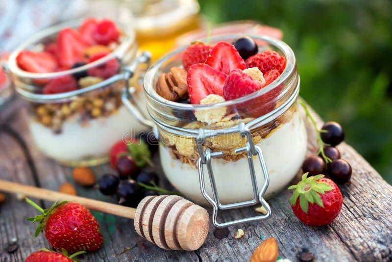 自创酸奶用在部分瓶子的莓果 免版税库存照片