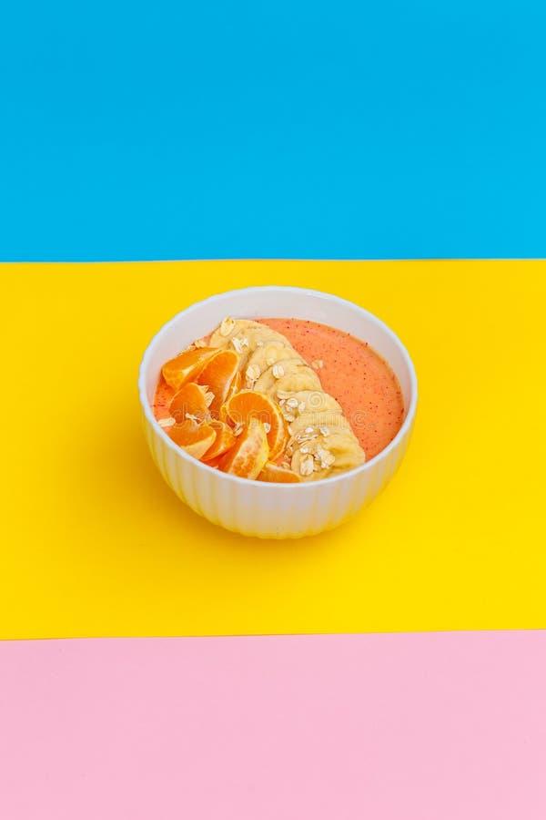 自创酸奶蜜桔和香蕉在一块板材在色的背景 r r 库存照片