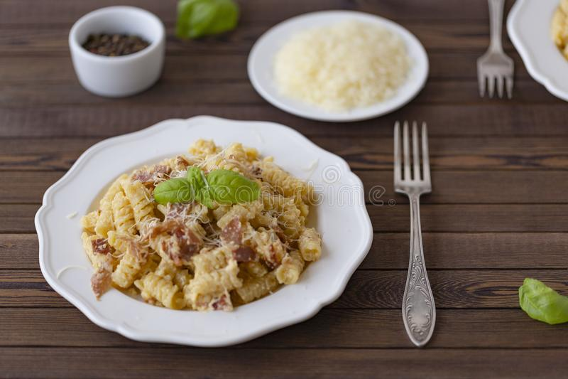 自创面团carbonara意大利语用烟肉,鸡蛋,在白色板材的帕尔马干酪在黑暗的背景 免版税图库摄影