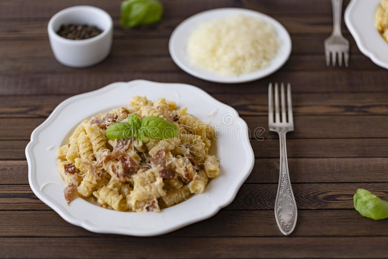 自创面团carbonara意大利语用烟肉,鸡蛋,在白色板材的帕尔马干酪在黑暗的背景 库存照片