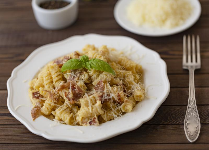 自创面团carbonara意大利语用烟肉,鸡蛋,在白色板材的帕尔马干酪在黑暗的背景 库存图片