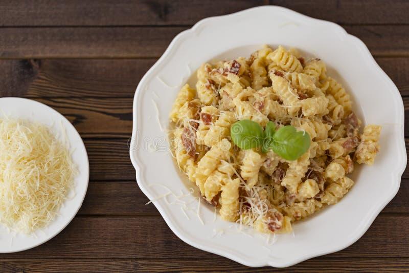 自创面团carbonara意大利语用烟肉,鸡蛋,在白色板材的帕尔马干酪在黑暗的背景 图库摄影