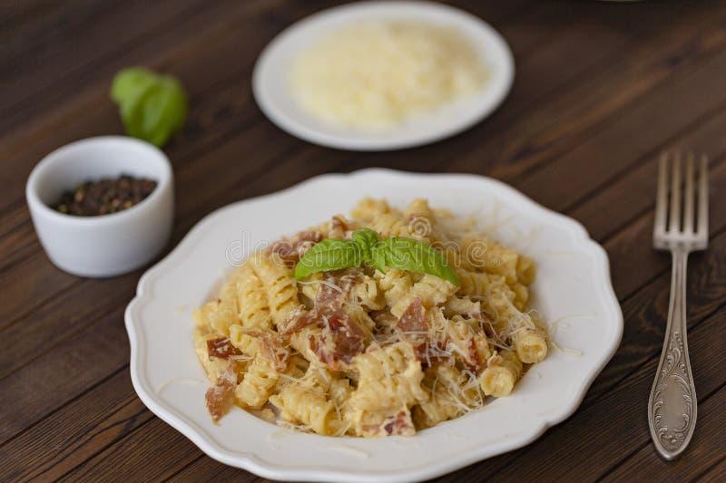 自创面团carbonara意大利语用烟肉,鸡蛋,在白色板材的帕尔马干酪在黑暗的背景 免版税库存图片