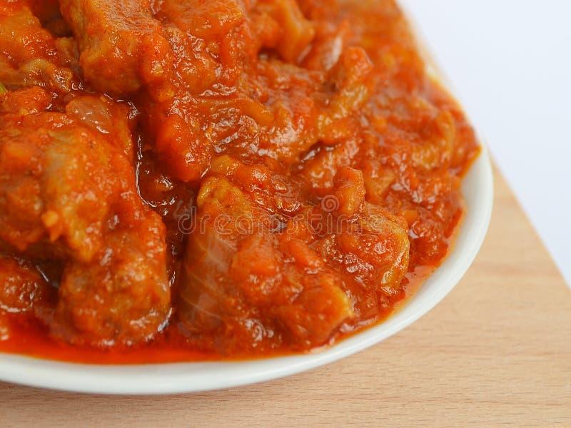 自创食物:肉炖用红萝卜、葱和辣椒粉在一块白色板材 库存照片