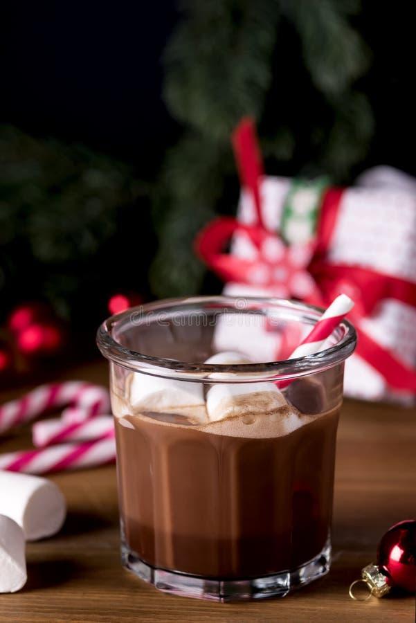 自创鲜美巧克力热饮的关闭在与蛋白软糖欢乐圣诞节背景棒棒糖垂直的玻璃 库存图片