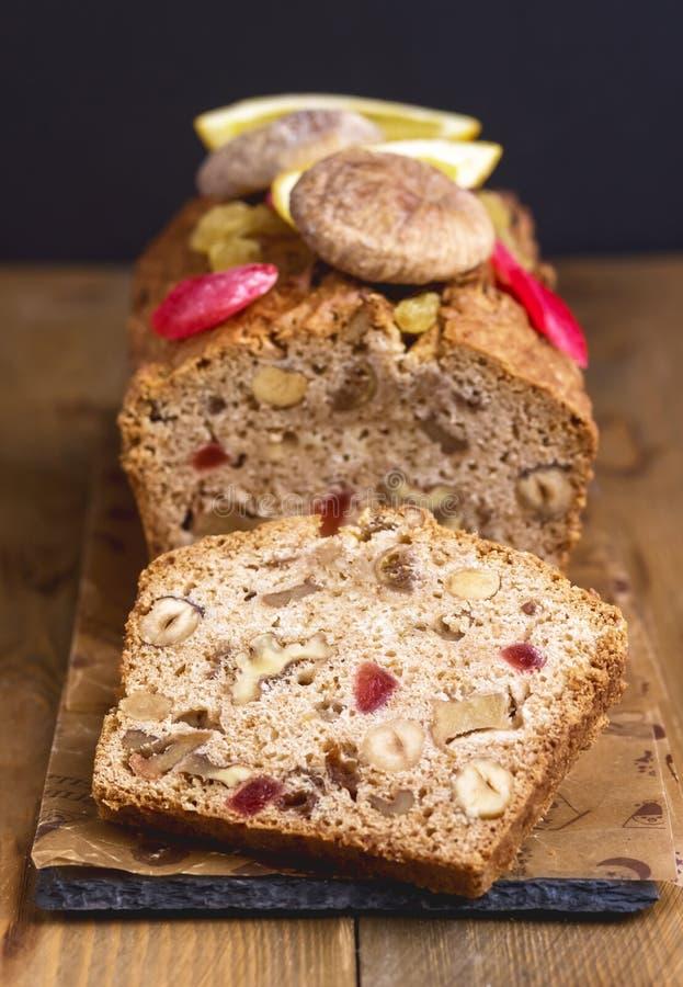自创鲜美果子蛋糕蛋糕用被定调子的干果和胡说的木背景垂直 库存图片