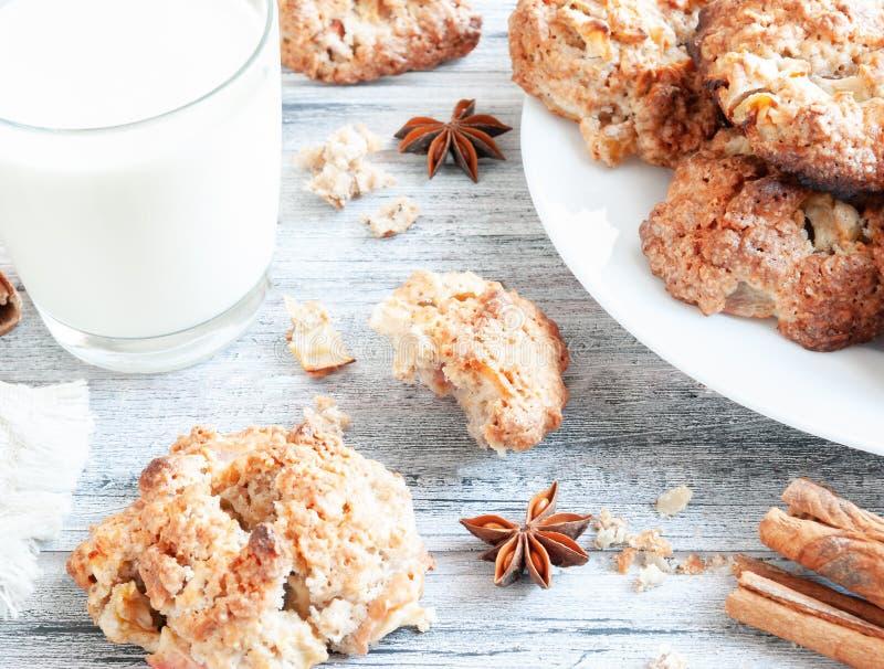 自创麦甜饼用苹果和坚果 一杯牛奶和曲奇饼在灰色木背景 特写镜头 在视图之上 免版税库存图片
