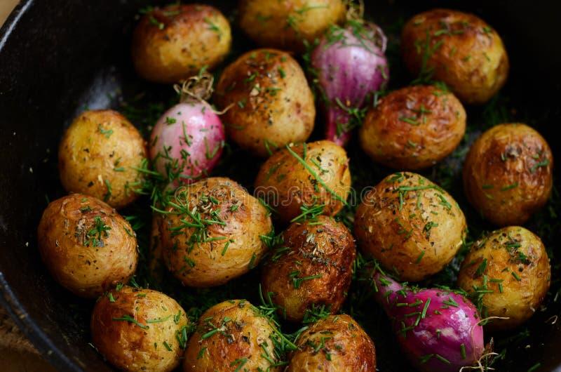 自创整个被烘烤的年轻土豆和紫罗兰色葱 库存图片