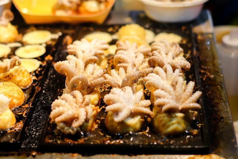自创& x22; 婴孩Octopus& x22;在黑火炉的Takoyaki日本球-日本食物背景或纹理的 库存图片