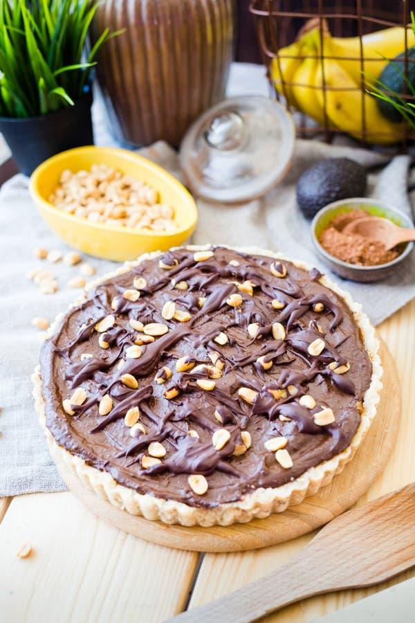 自创素食主义者鲕梨巧克力蛋糕用花生和香蕉,垂直的看法 免版税库存照片