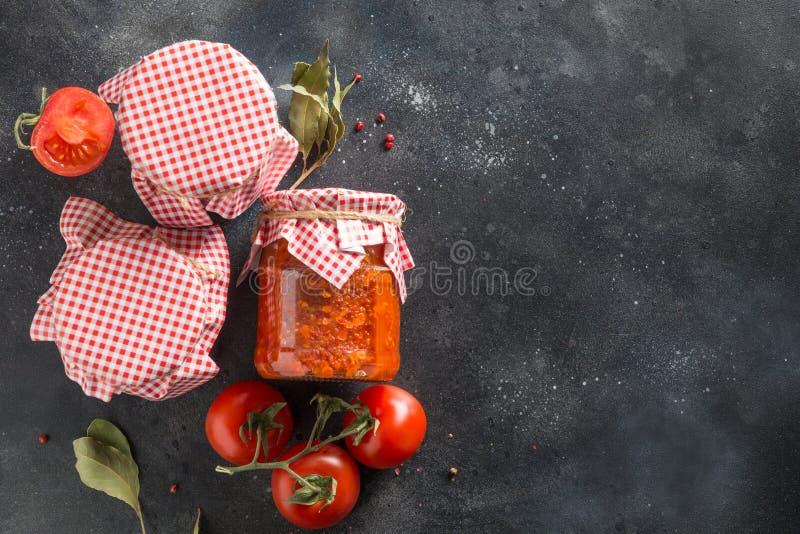 自创adjika用在瓶子的蕃茄在黑暗的背景 突尼斯和阿拉伯烹调adjika ??harissa 库存照片