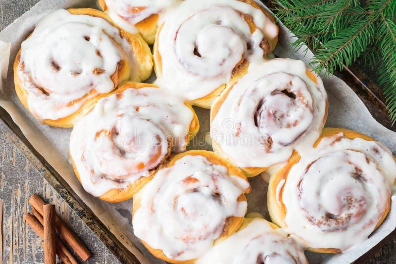 自创cinnabon小圆面包用桂香和奶油在白色板材在木桌和餐巾上 m r 免版税库存照片