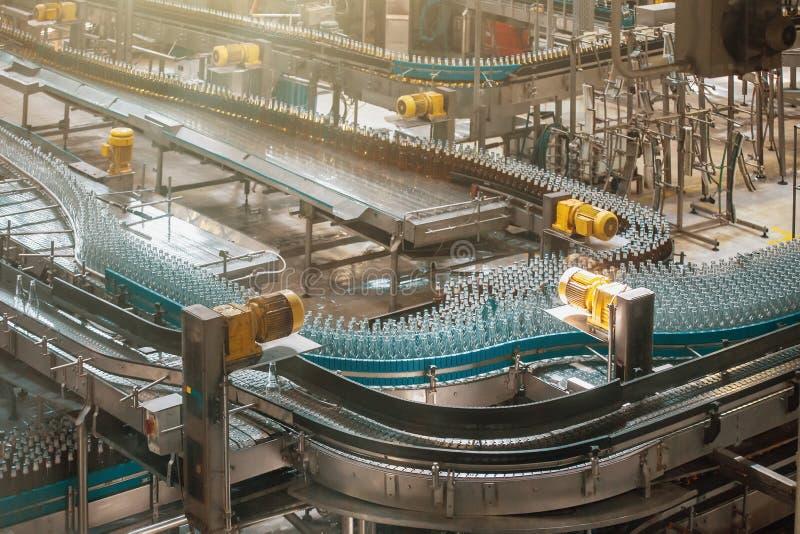 自动传动机线或传送带有玻璃瓶的在啤酒厂生产 工业啤酒装瓶的设备机械 免版税图库摄影