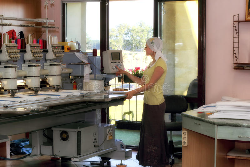 自动刺绣机器的女性操作员 图库摄影