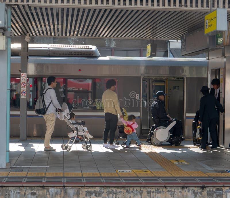自动化的轮椅的通勤者是协助由站长,当有婴儿车的时父母 免版税库存照片